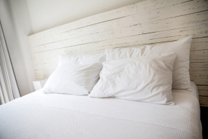 White bedroom with a king size bed and pillows.