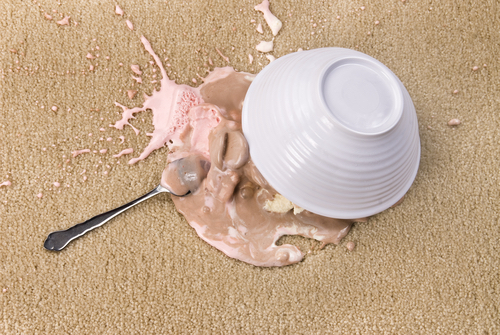 A bowl of spilled Neapolitan ice cream on white carpet that is melting.